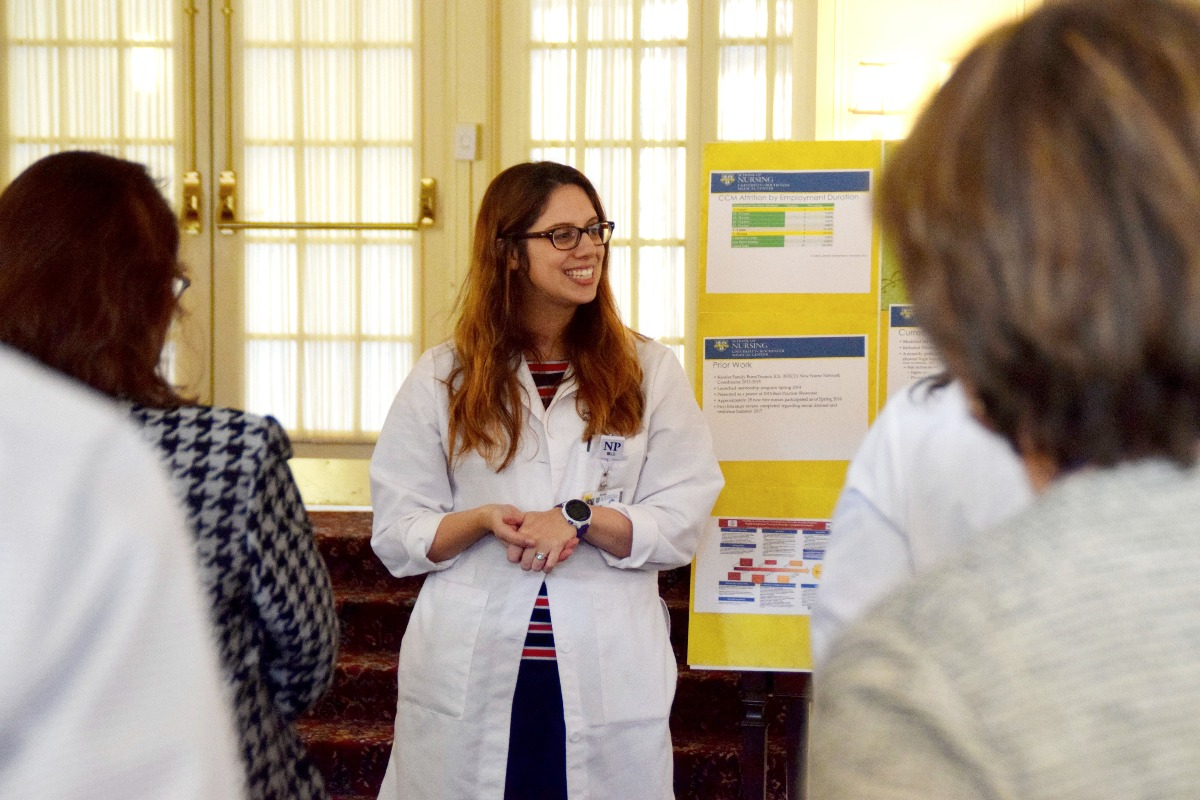 DNP student Jenna Gonillo, MS, ACNPC-AG, CCRN discusses her poster presentation on advanced practice provider burnout on DNP Project Day.
